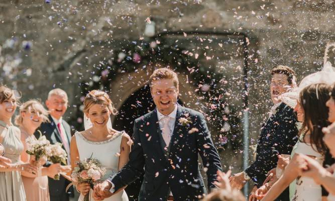 A newly married couple leaving a church smiling while people throw flower petals.